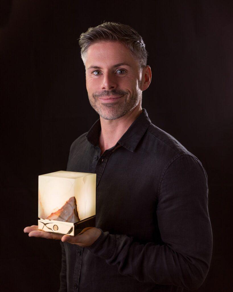 Luxonum Gründer Andreas Rauwolf hält eine Onyx Designer Leuchte ITSU One
